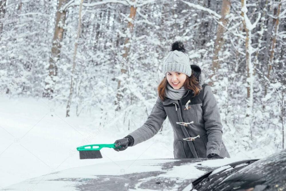 Молодая женщина, чистки автомобиля снег — Стоковое фото © shmeljov ...